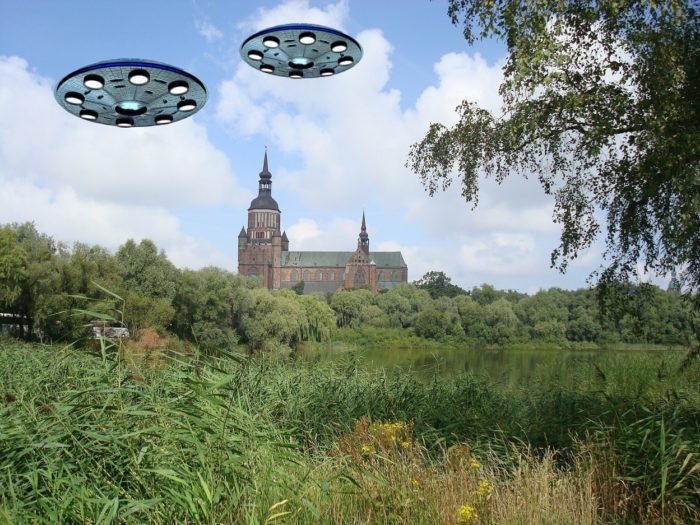 Two UFOs superimposed over a countryside picture