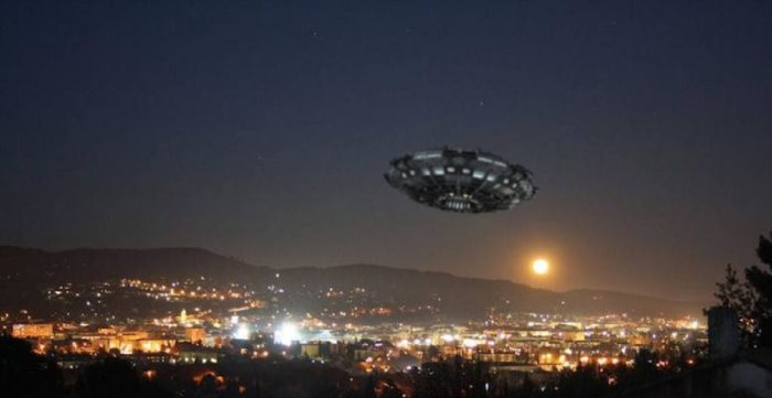 A superimposed UFO over a picture of a city at night