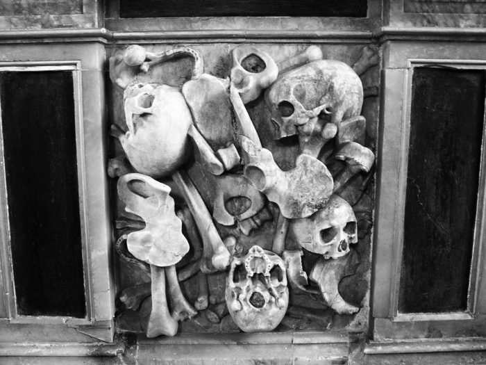 Skull and bones cemented in a wall