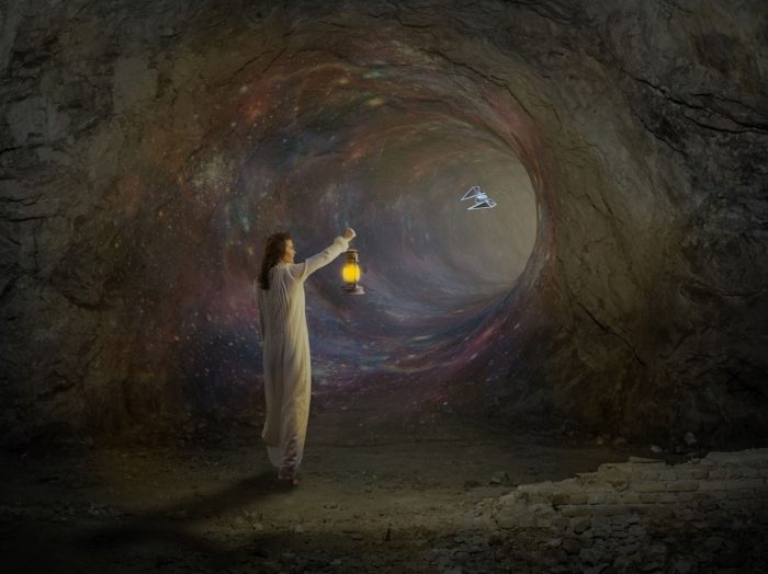A picture of a person with a lantern staring into a portal in a cave