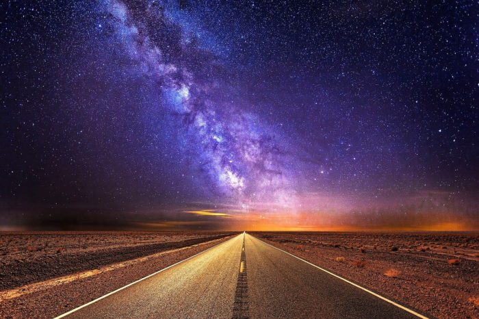 A picture of a road stretching into the distance with the Milky Way over the top
