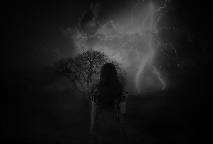 An image of a woman facing away looking toward a stormy sky