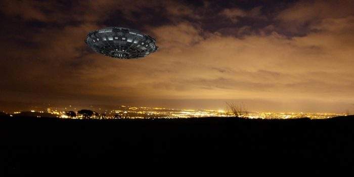 A UFO superimposed onto a night sky with the city lights in the background