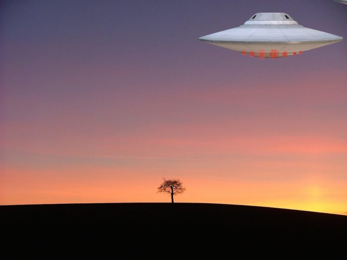 A silver UFO hovering over a lone tree at sunset