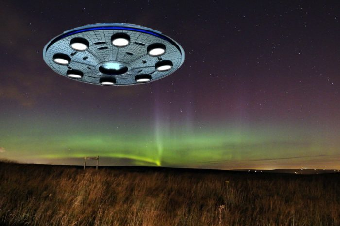 A flying saucer superimposed onto a picture of a field at night
