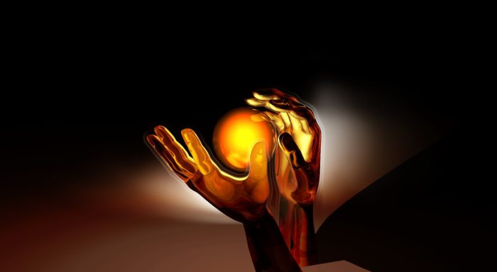 a pair of hands about to catch a glowing orb