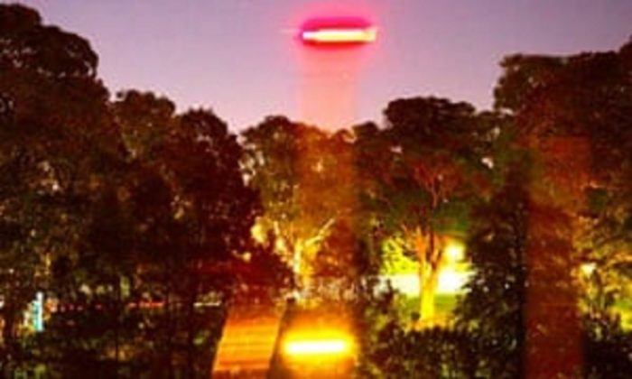A picture showing an alleged UFO shining a light to the ground