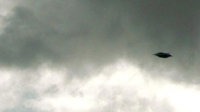 A picture showing an alleged UFO in a cloudy sky