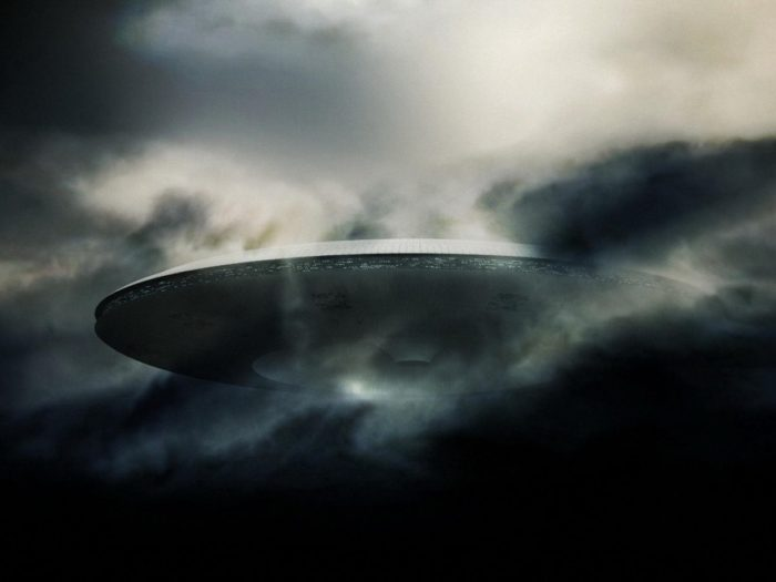 An image showing a huge mothership type UFO emerging from the clouds