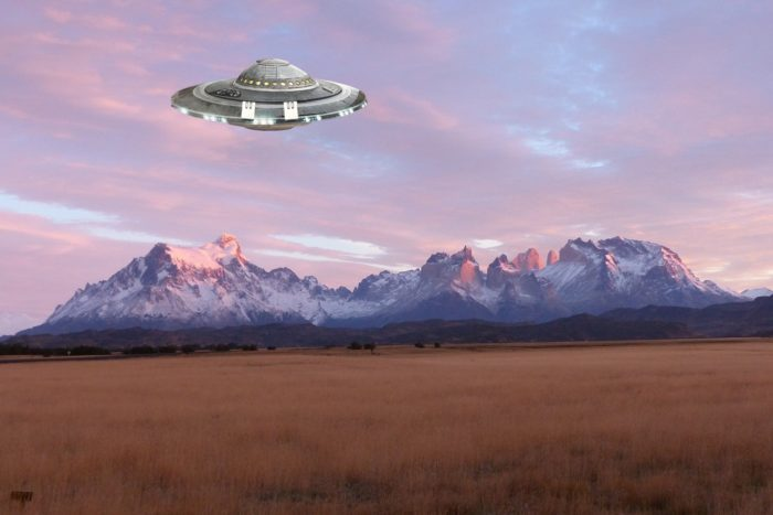 An image showing a UFO over a mountain range