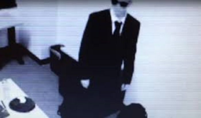 A picture showing a strange man in black suit, tie, and dark glasses