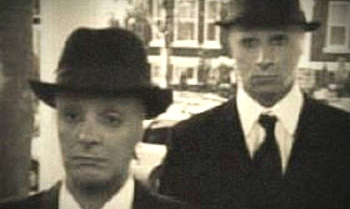 "A picture showing two ""Men In Black"" at a doorstep"