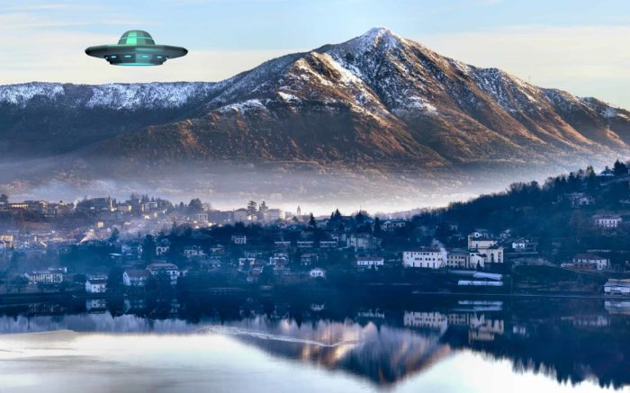 A UFO superimposed into a picture of a village with a mountain in the background