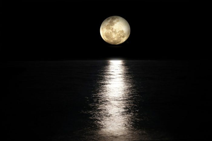 The reflection of the Moon on the water with a full moon overhead