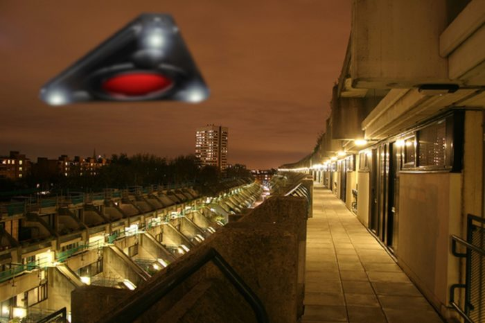 A triangular UFO hovering over a housing estate at night