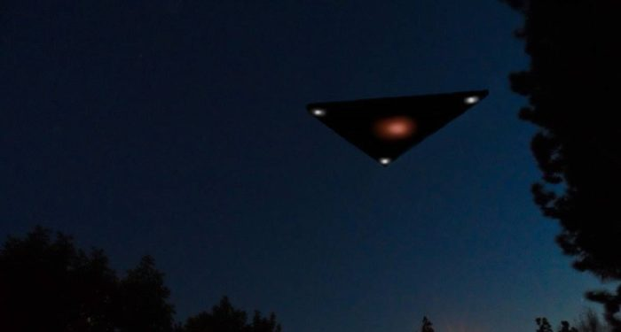 A black triangle UFO flying through the night sky