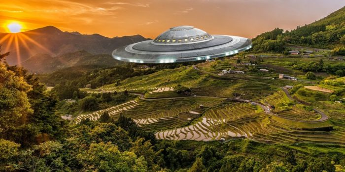 A flying saucer superimposed onto an aerial view of the countryside