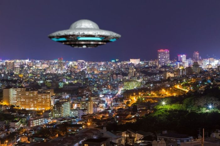 A UFO superimposed on to a glowing city at night