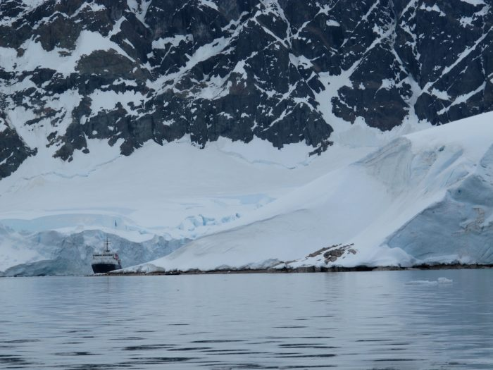 A ship looks tiny compared to icy landmass behind it
