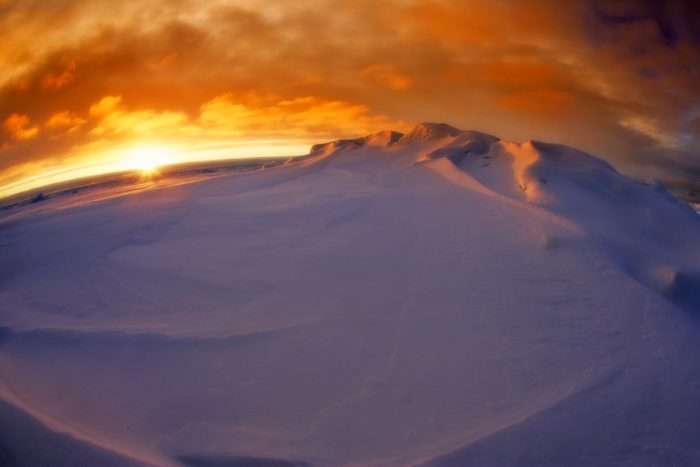 Sunset in Antarctica over snowy mountains