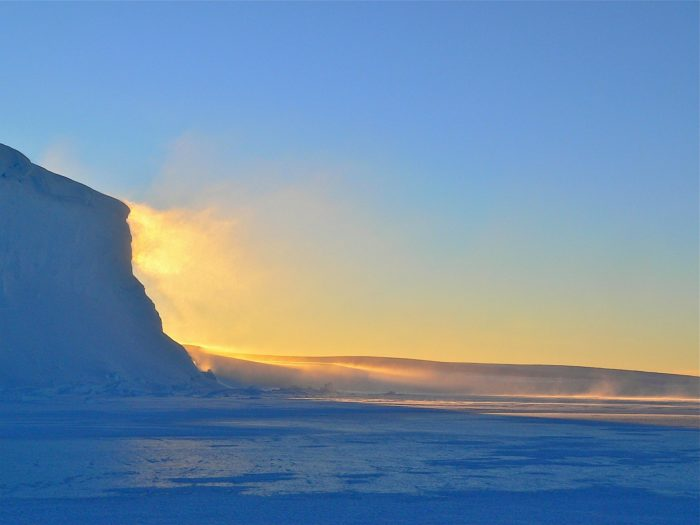 The sun reflects off the ice of Antarctic terrain