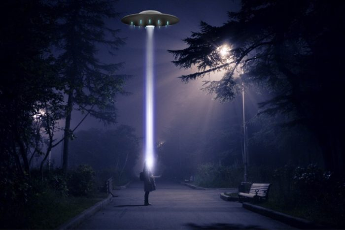 A picture of a person on a dark street looking up at a UFO with a light shining on them