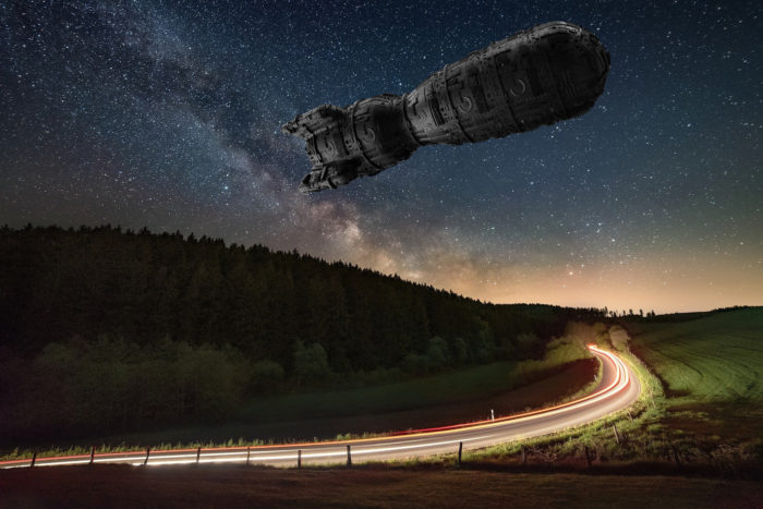Superimposed UFO over a road at night