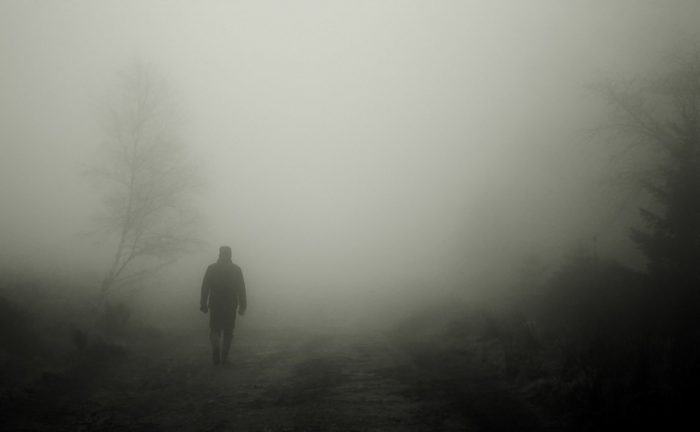 A picture of a mysterious person walking into the mist