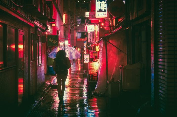 A picture of a person walking down a Japanese street at night