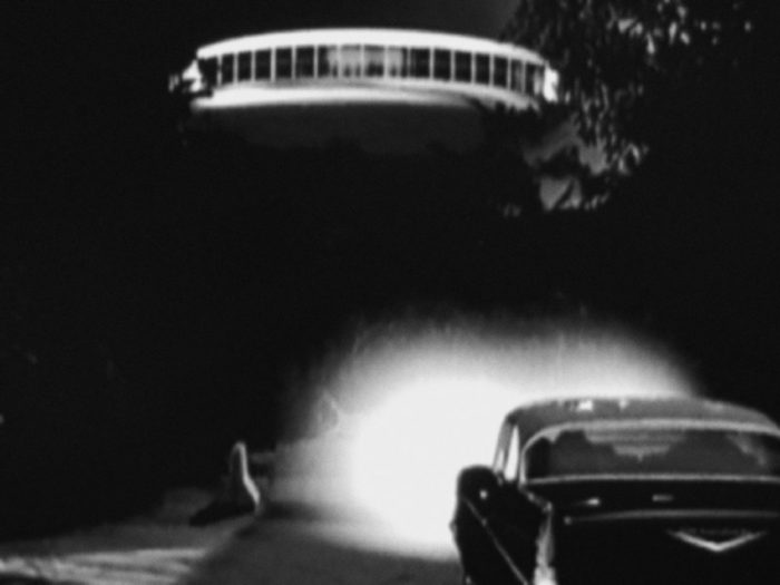 A depiction of a UFO over a parked car