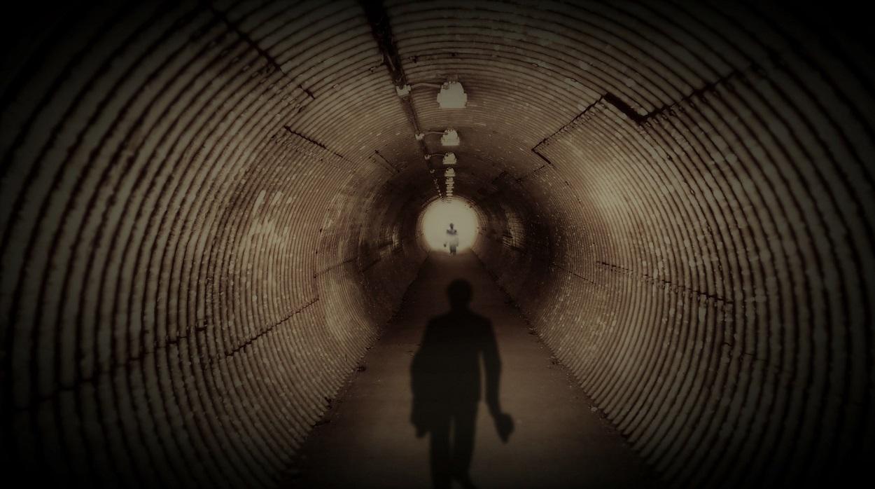 A tunnel with a dark figure walking along it