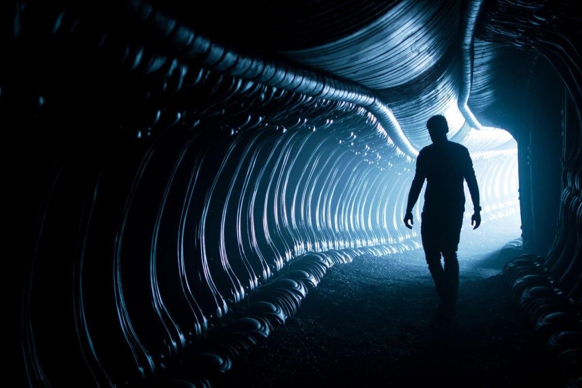 A dark figure working through a tunnel