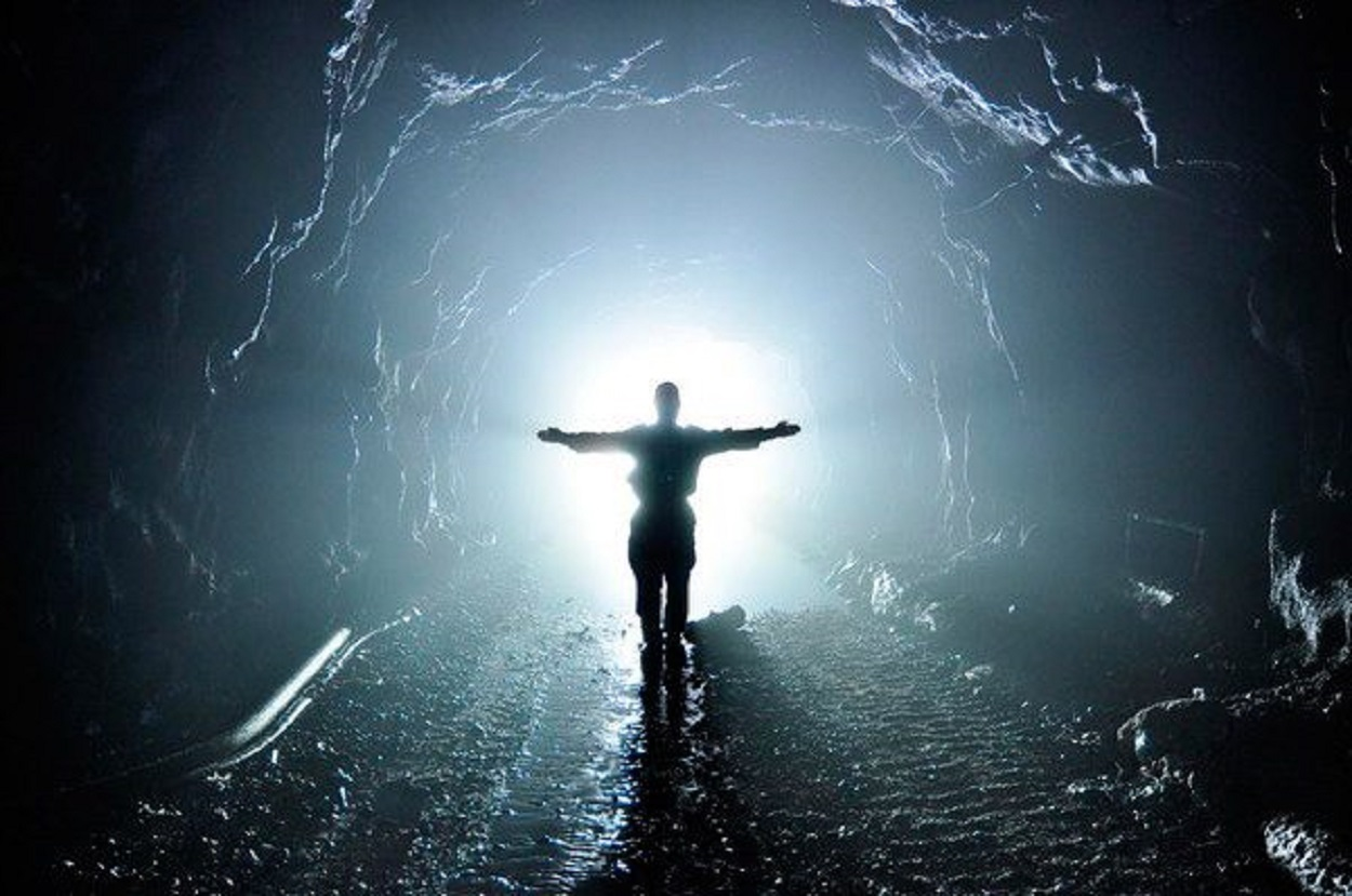 A person stood in a tunnel with a light behind them