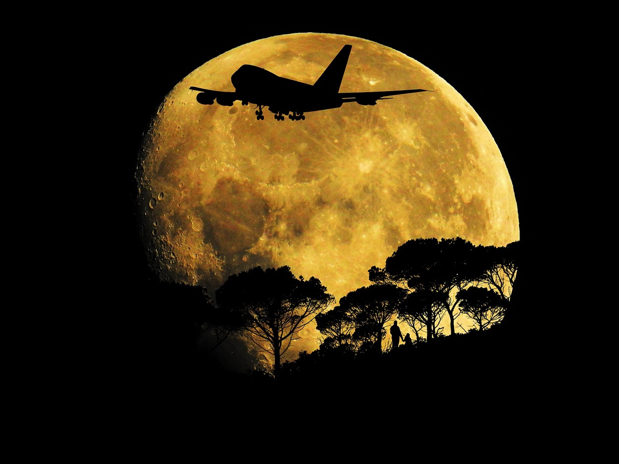A plane flying in front of the moon